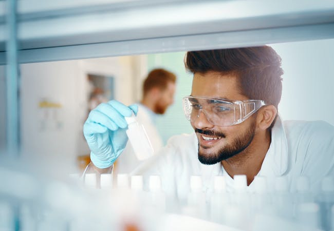 A researcher examines a sample in a lab and smiles.