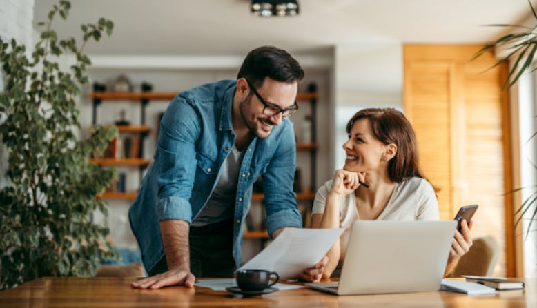 A smiling couple look at documents together while at home.