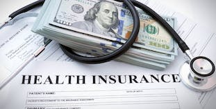 Health insurance with money and a stethoscope.