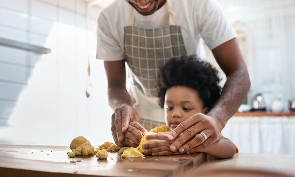 A father and young son knead dough together in their the kitchen.