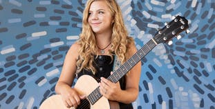 A  teen girl and American Idol contestant smiles while holding a guitar.
