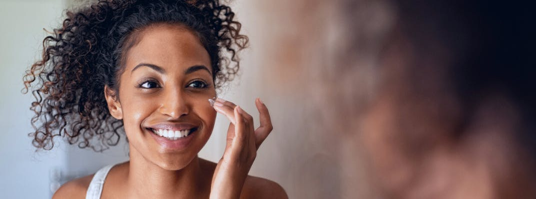 A woman smiles while putting lotion on her face.
