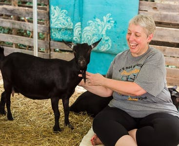 Julie Greenwood poses with a goat during a yoga fundraising event.