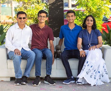The Kumar family pose outside on a couch.