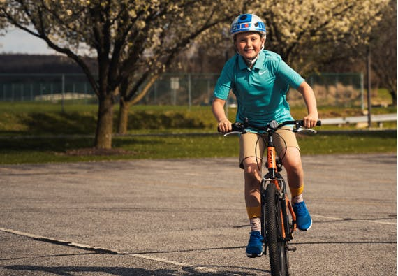 A young boy smiles while riding a bike outside.