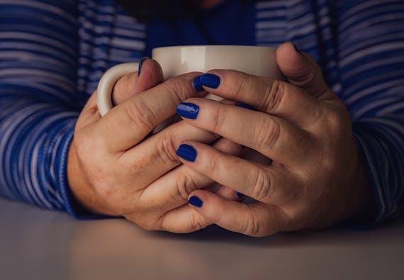 A woman's hands with blue nail polish holds onto a coffee mug.