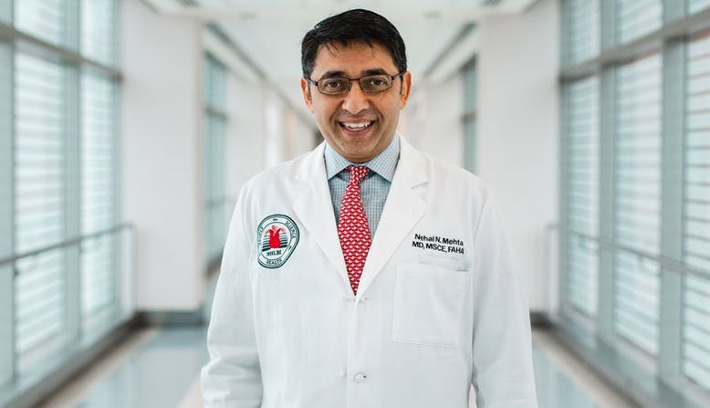 Researcher Nehal Mehta smiles while wearing his white coat.
