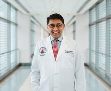 Il ricercatore Nehal Mehta sorride mentre indossa il suo camice bianco.