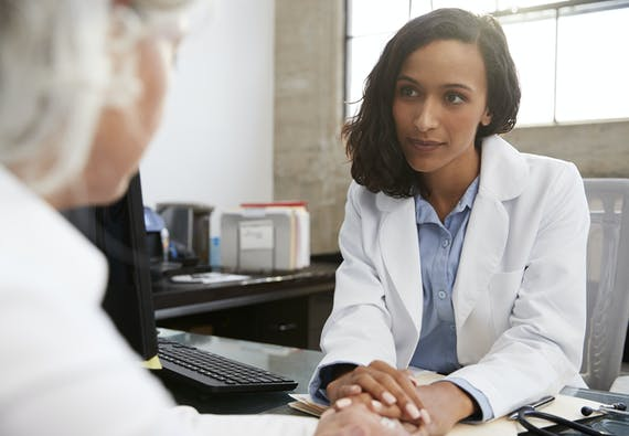 Photo of a healthcare professional consulting with a patient at a desk.