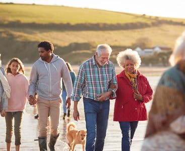 A crowd of people walk together on the beach with a dog.