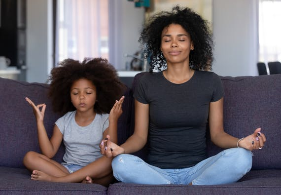 A mother sits on the couch with her daughter meditating.