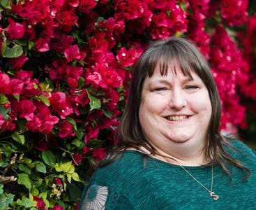 Rachel English of Tucson, Arizona smiles in front of a wall of red flowers.