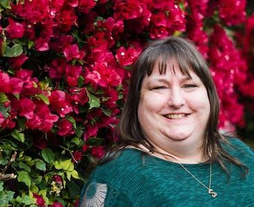 Rachel English di Tucson, Arizona sorride davanti a un muro di fiori rossi.