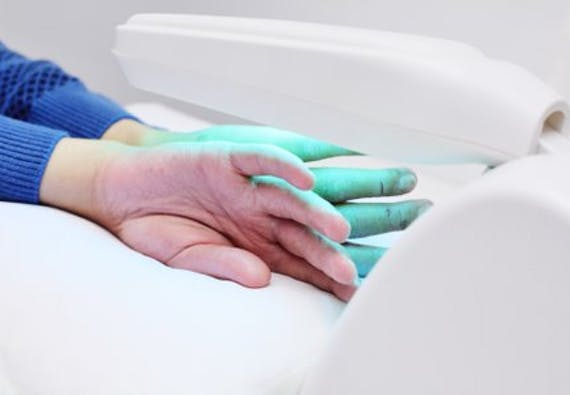 A pair of hands placed under a light medical device.