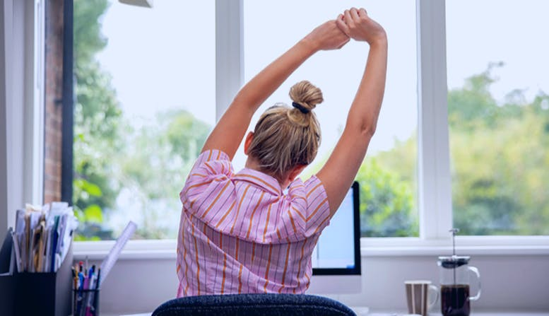 A young woman sits at her desk and stretches with her arms over her head.