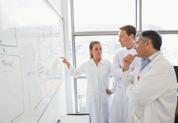 Three people in lab coats looking at a whiteboard