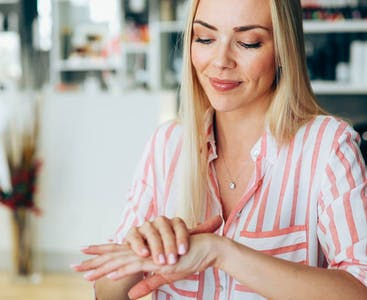 Woman applying lotion.