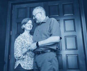 Nancy and Don Alpert smile and embrace each other in front of a door.