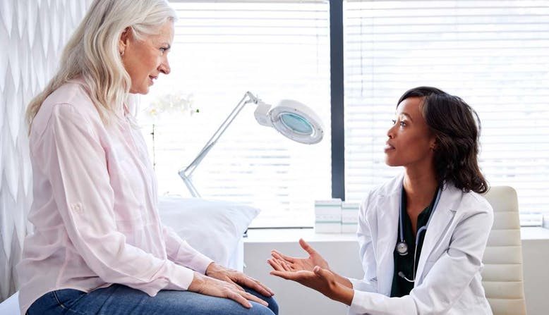 A woman talks to her doctor in an office.
