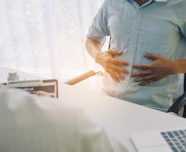 Man holding his stomach while talking to a doctor.