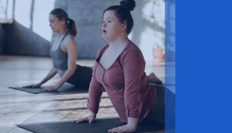 Two women stretch in a yoga studio.