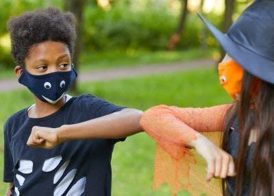 Kids wearing masks to avoid transmitting COVID-19 bump elbows.