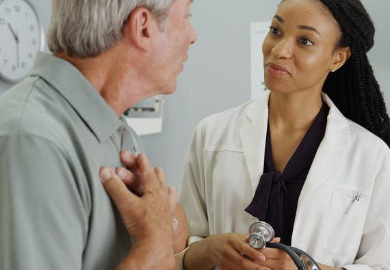 A female doctor listens as a patient speaks and holds his chest.