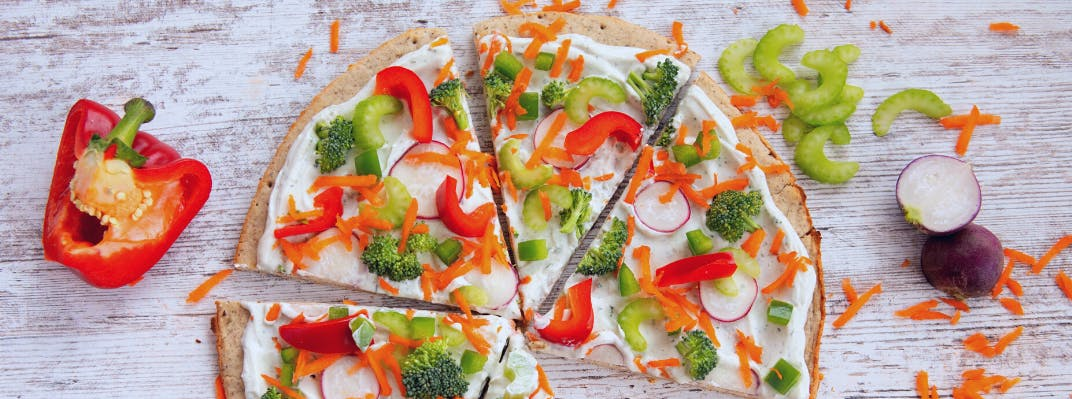 A veggie pizza with chopped vegetables on a table.