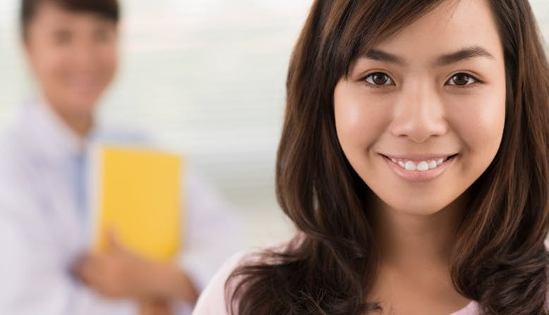 A teen smiles for a camera while the doctor sands behind her.