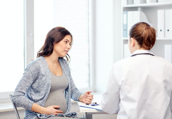 A pregnant woman touches her stomach while conversing with a doctor.