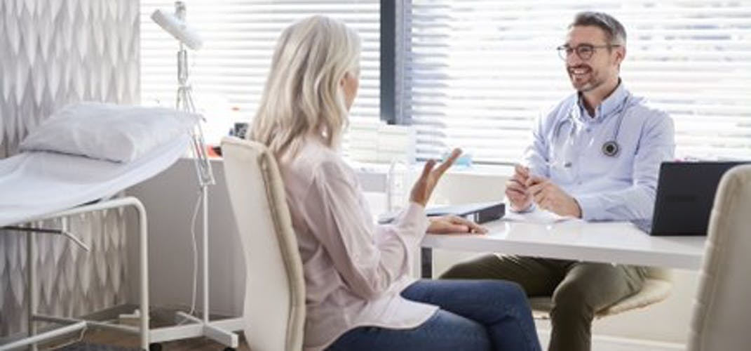A female patient talks with a smiling doctor in an office.