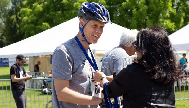 Matt Mercier receives a medal after participating in a Team NPF Cycle event.
