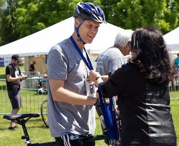 Matt Mercier riceve una medaglia dopo aver partecipato a un evento Team NPF Cycle.