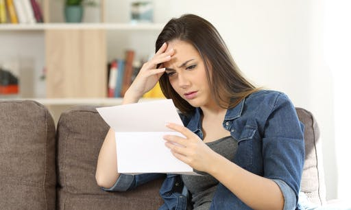 A woman looks confused while reading over her medical insurance plan.
