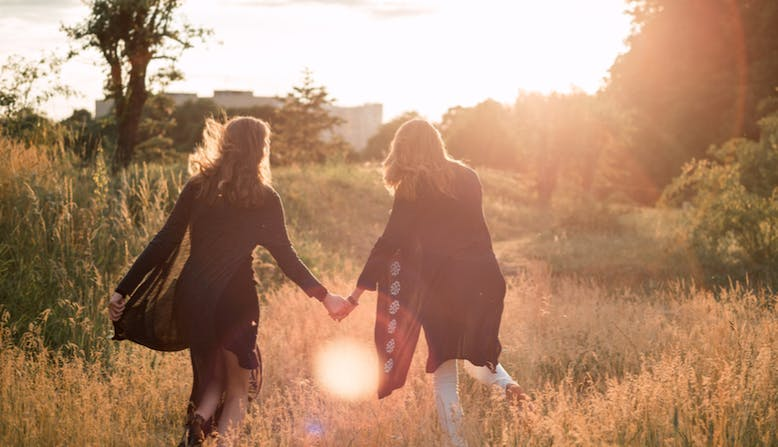 Two women hold hands while walking through a meadow.
