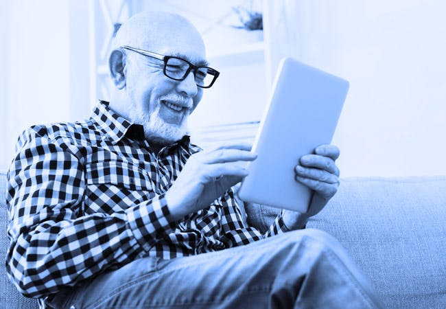An older man smiles while looking at a tablet.