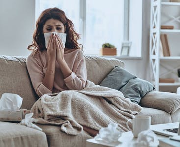 A woman on the couch with the flu blows her nose into a tissue.