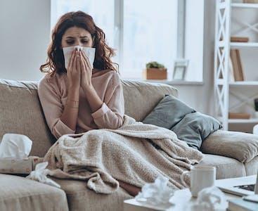 Una donna sul divano con l'influenza soffia il naso in un fazzoletto.