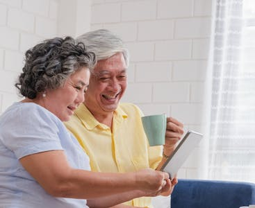 A man and a woman comparing insurance options on a tablet while sitting down.