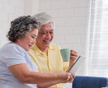 Un uomo e una donna confrontano le opzioni di assicurazione su un tablet mentre sono seduti.