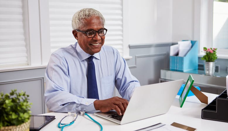 A male medical professional sitting at his desk, smiling and working on a laptop.