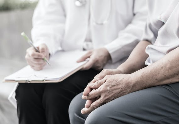 A doctor and patient discuss the findings of a chart while sitting down.