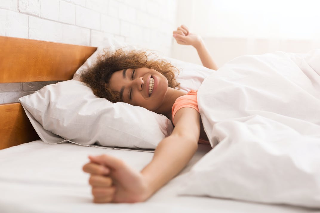A woman looks refreshed and stretches after a good night's sleep