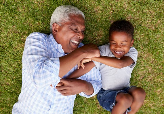 A grandpa and grandson laugh while laying in the grass
