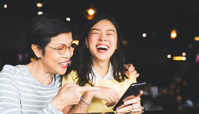 A mother and daughter laugh together as they look at the daughter's phone.