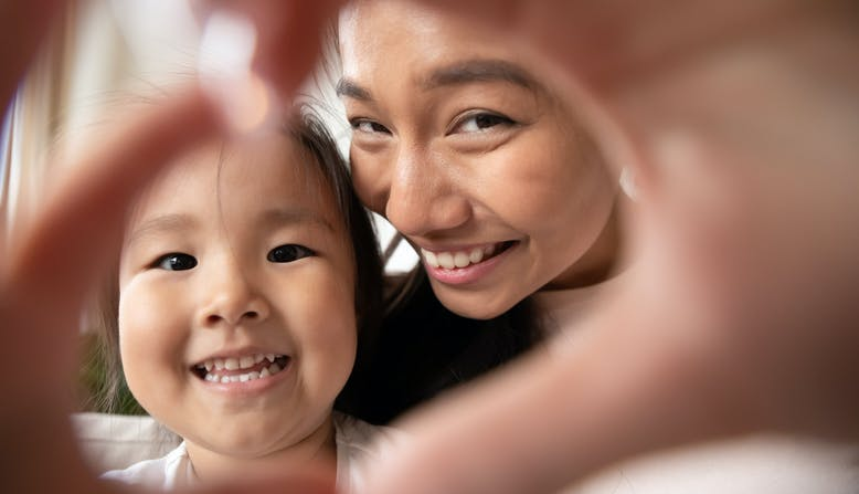 An adult and child smile while making the shape of a heart with their hands.