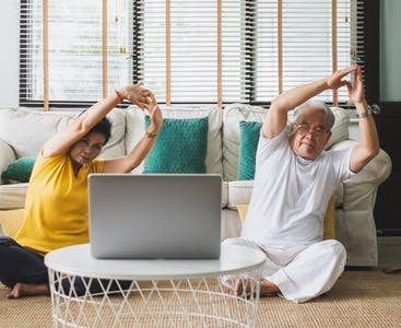 Two older couple stretching in front of a couch and laptop.