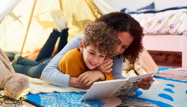 A mother and child lay in a tent and read a book together.
