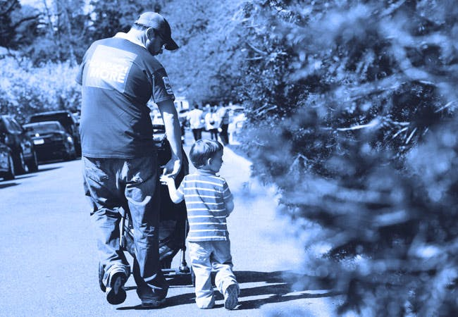 A father and son walk down the street with a baby stoller.