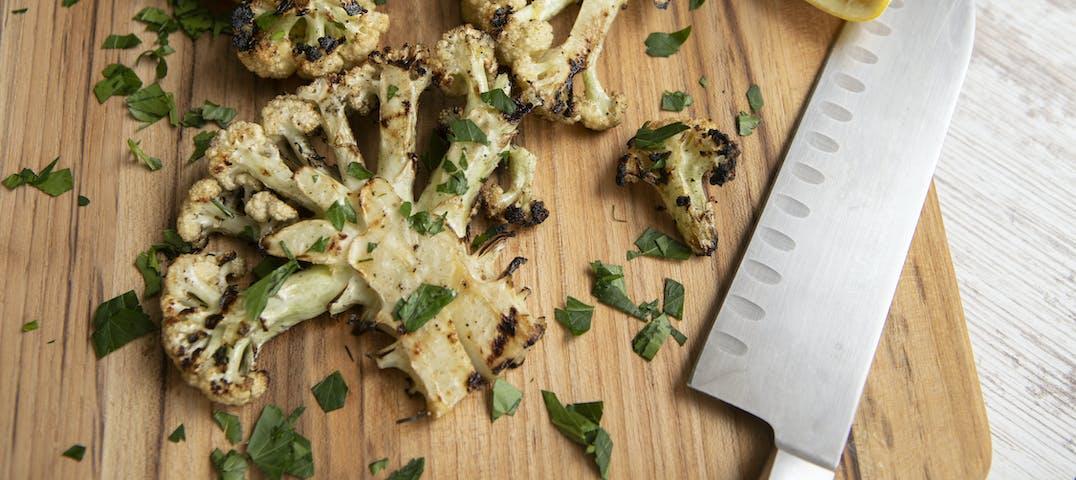A cutting board with seasoned cauliflower and knife.